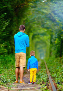 father and son walking on rails in green tunnel